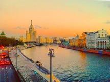 Sikt av solnedgången på floden, en bostads- skyskrapa på den Kotelnicheskaya invallningen, Moskvaflod, Bolshoy Ustinsky bro Mo Royaltyfri Foto
