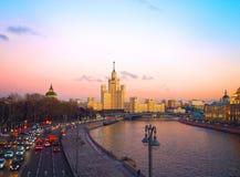 Sikt av solnedgången på floden, en bostads- skyskrapa på den Kotelnicheskaya invallningen, Moskvaflod, Bolshoy Ustinsky bro Mo Royaltyfria Bilder