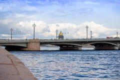 Sikt av sommarstaden med cloudly himmel I den förgrundsBlagoveshchensky bron i St Petersburg I bakgrunden royaltyfria bilder