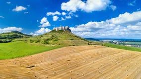Sikt av Spissky hrad och ett fält med runda baler i Slovakien Arkivbild