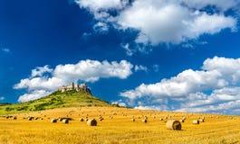 Sikt av Spissky hrad och ett fält med runda baler i Slovakien, Centraleuropa Royaltyfria Foton