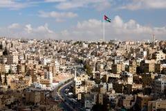 Sikt av staden av Amman med jordanska flaggor Arkivfoton