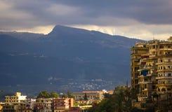 Sikt av staden och bergen under en dyster himmel lebanon tripoli royaltyfri bild