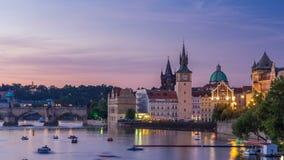 Sikt av staden Prague i Tjeckien med färgrik dag för skovelfartyg till natttimelapse på den Vltava floden med