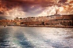 Sikt av stads- och havsporten på bakgrunden av dramatiska solar Arkivbild