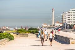 Sikt av stranden av Leca da Palmeira, med folk som gör övning och går, upptagen gata bredvid stranden, fyr i royaltyfri fotografi