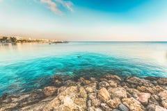 Sikt av stranden med några personer som simmar i turkoshavet Protaros Cypern royaltyfri foto