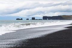 sikt av stranden och Dyrholaey för Reynisfjara svartsand Royaltyfri Bild