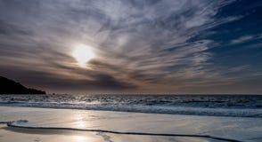 Sikt av stranden på solnedgången med moln som in rullar Royaltyfria Bilder
