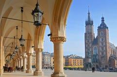 Sikt av Sts Mary basilika från torkduken Hall som bygger Sukiennice på huvudsaklig marknadsfyrkant av Cracow, Polen royaltyfria foton