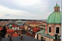 Sikt av taken av gamla Prague från sidan av en katolsk domkyrka royaltyfri bild