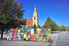 Sikt av tecknet och kyrkan för stad det välkomna i Zloven, Slovakien arkivbilder