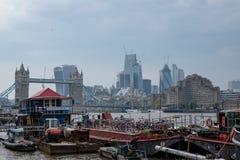 Sikt av tornbron och högväxta stadsbyggnader i bakgrunden I förgrunden är husbåtar på Shad Thames royaltyfri foto
