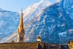 Sikt av tornet för klocka för Hallstat ` s det berömda kyrkliga mot härligt M Royaltyfri Foto