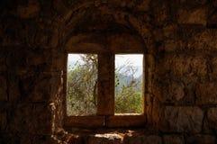 Sikt av träd och berg till och med antikt fönster på den gamla stenen Arkivbilder