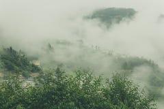 Sikt av traditionella bhutanesiska byggnader med dimmiga kullar, Bumthang, Bhutan, Asien Royaltyfri Bild