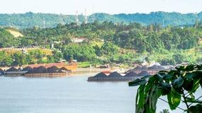 Sikt av trafik av bogserbåtar som drar pråm av kol på den Mahakam floden, Samarinda, Indonesien royaltyfri bild