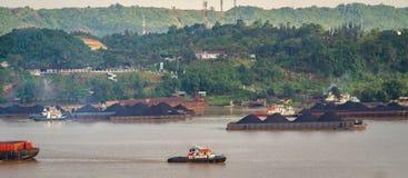Sikt av trafik av bogserbåtar som drar pråm av kol på den Mahakam floden, Samarinda, Indonesien royaltyfri foto