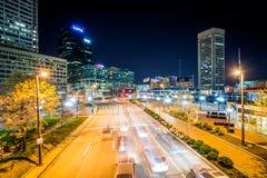 Sikt av trafik och byggnader längs den ljusa gatan på natten, i th Arkivfoton