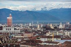 Sikt av Turin med Torre Littoria och snowcapped fjällängar Fotografering för Bildbyråer