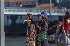 Sikt av två asiatiska höga kvinnor som går i centrum av den Porto staden, bron och floden som bakgrund royaltyfri foto