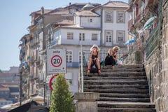 Sikt av två kvinnor som sitter på en trappuppgång i Ribeira, äter, dricker och kopplar av, på i stadens centrum arkivbild