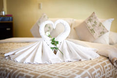 Sikt av två vita handduksvanar på sängarket i hotell Royaltyfri Foto