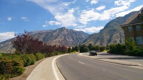 Sikt av Utah berg upp en gata på en kulle med blå himmel och moln Royaltyfria Bilder