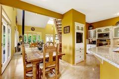 Sikt av vardagsrum från ingångshall med räcke och trappa Äta middag område i kökrum Fotografering för Bildbyråer