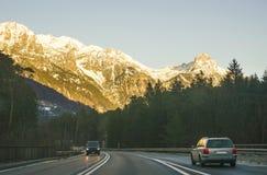 Sikt av vägen med bilen på solnedgången i vintern Schweiz Royaltyfria Bilder