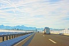 Sikt av vägen med den mini- skåpbilen i Schweiz i vinter Arkivfoton