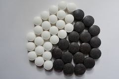 Sikt av yin och det yang symbolet som bildas av svartvita piller från över arkivbild