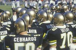 Sikt bakifrån av gruppen av högskolafotbollsspelare som håller ögonen på leken från sidlinjer, West Point, NY Arkivbild