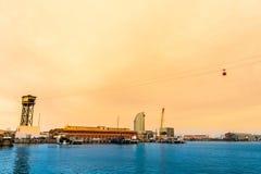 Sikt Barcelona för gammal port på solnedgången med cablewayen och det lugna havet Fotografering för Bildbyråer