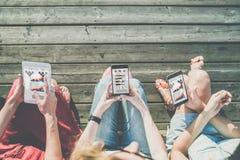 Sikt, datorminnestavla och smartphones med diagram, grafer och diagram i händer av tre flickor som sitter utanför på träplattform Royaltyfri Bild