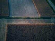 Sikt för öga för fågel för surrflyg flyg- av traktoren som mejar gräs på härlig grön bonde för fält och för blå himmel bakgrunds Arkivbilder