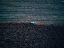 Sikt för öga för fågel för surrflyg flyg- av traktoren som mejar gräs på härlig grön bonde för fält och för blå himmel bakgrunds Arkivfoto