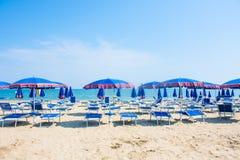 Sikt för Adriatiskt havkust Kust av Italien, sommarparaplyer på den sandiga stranden med moln på horisont Arkivfoton