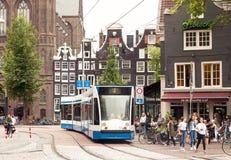 Sikt för Amsterdam centrumgata med att förbigå för spårvagn för folk och för offentligt trans. arkivfoton