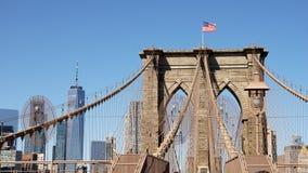 Sikt för Brooklyn bro med flaggan av Förenta staterna i New York City arkivbild