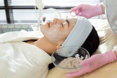 Sikt för CosmetologistApplying Face Mask sida royaltyfri fotografi