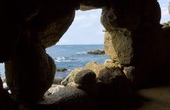 Sikt för Costabravastrand till och med ett grottahål Royaltyfria Foton