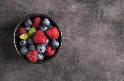 Sikt för grå bakgrund för hallon och för blåbär bästa royaltyfri foto