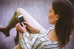 Sikt för hög vinkel av affärskvinnan som använder mobiltelefonen på kontoret Arkivfoton