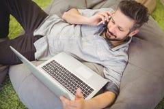 Sikt för hög vinkel av affärsmannen som använder bärbara datorn och mobiltelefonen på det idérika kontoret Arkivfoto