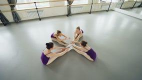 Sikt för hög vinkel av böjliga balettdansörer som gör huvud-till-knä krökningar som sitter på golv i studion som sträcker ben och stock video