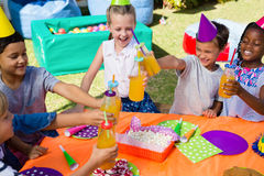 Sikt för hög vinkel av barn som rostar som dricker flaskor Royaltyfri Bild