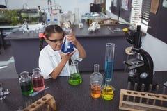 Sikt för hög vinkel av den elementära studenten som undersöker den blåa kemikalien i flaska på laboratoriumet Royaltyfri Foto