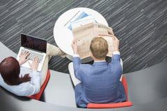 Sikt för hög vinkel av den läs- tidningen för affärsman medan kvinnlig kollega som i regeringsställning använder bärbara datorn Arkivfoto