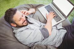 Sikt för hög vinkel av den lyckliga affärsmannen som använder bärbara datorn och mobiltelefonen på det idérika kontoret Royaltyfria Bilder